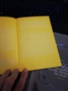 weiße Schrift auf gelbem Hintergrund - Das Booklet ist schwer zu lesen.