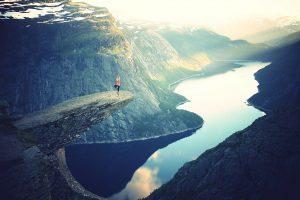 Ausblick, eine Yogini steht auf einem Felsvorsprung und sieht in ein wunderschönes Tal